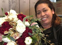 One of our floral designers poses with a lovely creation
